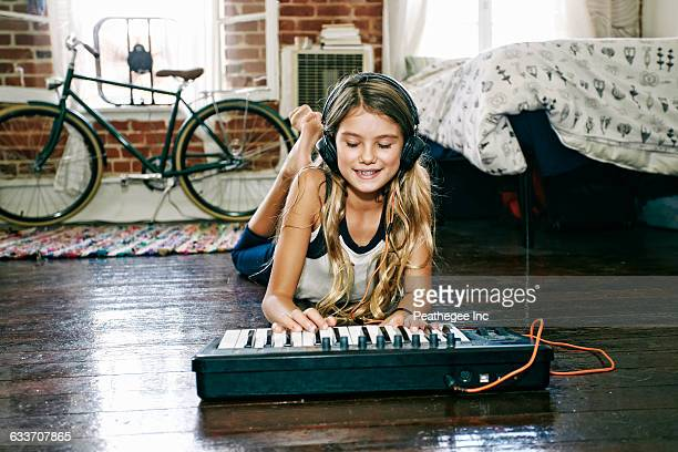 Native American girl playing keyboard in bedroom