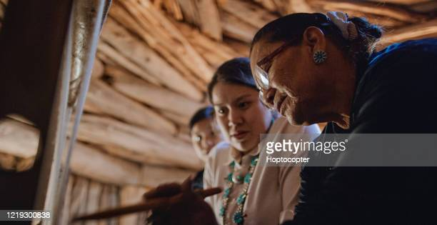 a native american grandmother (navajo) in her sixties teaches her teenaged granddaughters how to weave at a loom indoors in a hogan (navajo hut) - india imagens e fotografias de stock