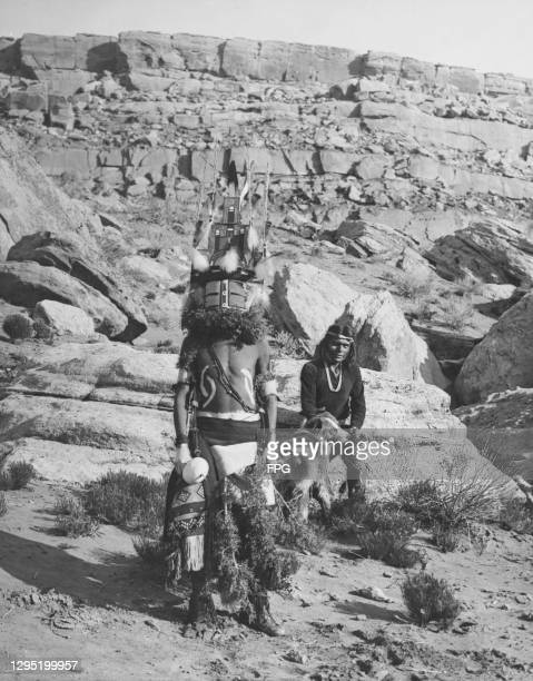 Native American Hopi man stands in ceremonial costume, with a second tribesperson sits behind with a dog, against the rugged landscape of the Hopi...