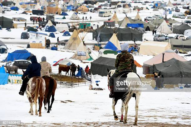 Native american horsemen take their horses for a ride through Oceti Sakowin Camp on the edge of the Standing Rock Sioux Reservation on December 2,...