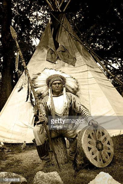 native american in traditional dress sitting outside teepee - headdress stock pictures, royalty-free photos & images