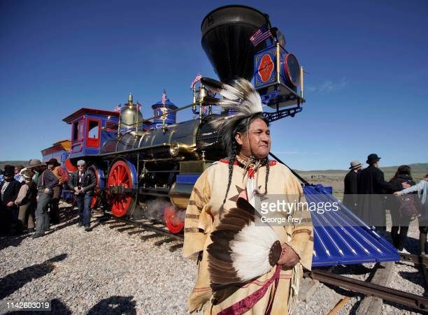 Native American in traditional dress stands in front of the Jupiter steam engine as part of the 150th anniversary of the driving of the Golden Spike...