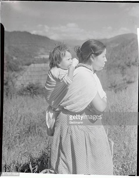 Native American Indian Woman from the Cherokee Nation holds a baby on her back.