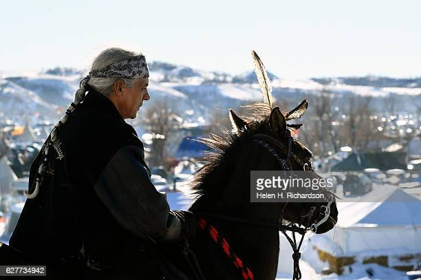Native american Ken Forkcloud, of the Crow Creek Nation, riding his horse Black Rose, looks over the Oceti Sakowin camp at the Standing Rock Sioux...