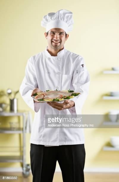 native american male chef holding plate of food - chef's hat stock pictures, royalty-free photos & images