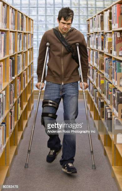 Native American man on crutches in library