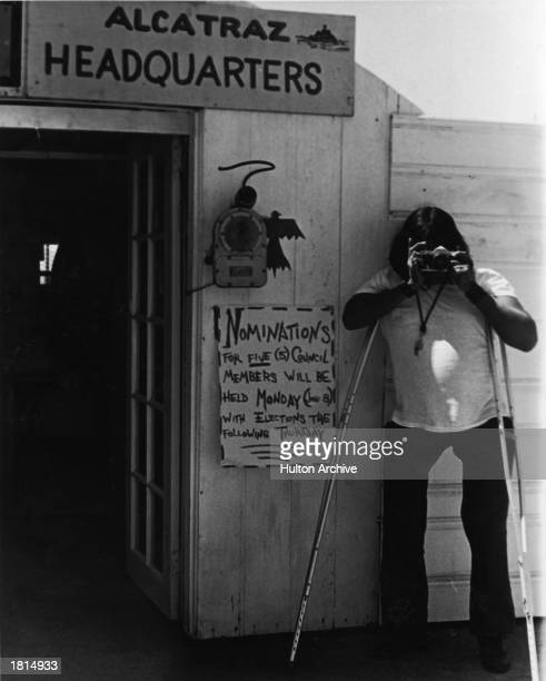 A Native American man on crutches takes a picture during a takeover of Alcatraz Island by a group of Native Americans San Francisco California June...