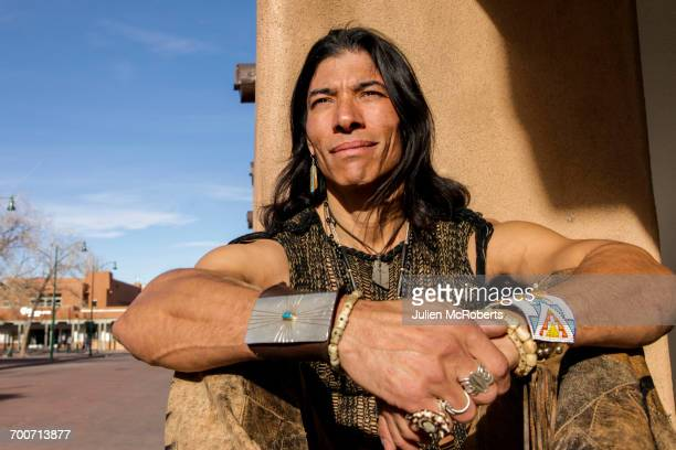 Native American man sitting against post