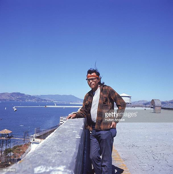 A Native American man stands on the roof of a prison complex building during the siege of Alcatraz Island by a group of Native Americans San...