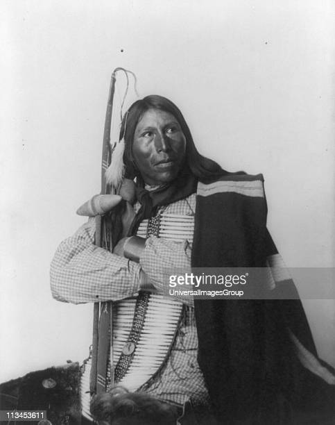 Native American man, three-quarter length portrait, seated, facing right: arms folded, holding bow, arrow, and tomahawk: dressed in bone breast...
