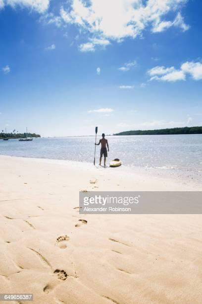 Native American man with kayak on beach