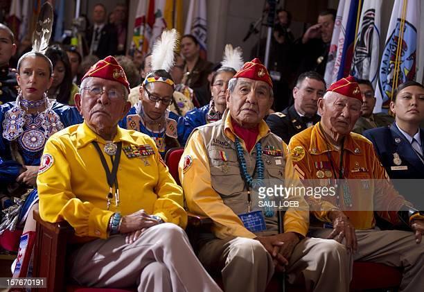 Native American members of the Navajo Code Talkers Bill Toledo Peter MacDonald and George James Sr listen as US President Barack Obama speaks to the...