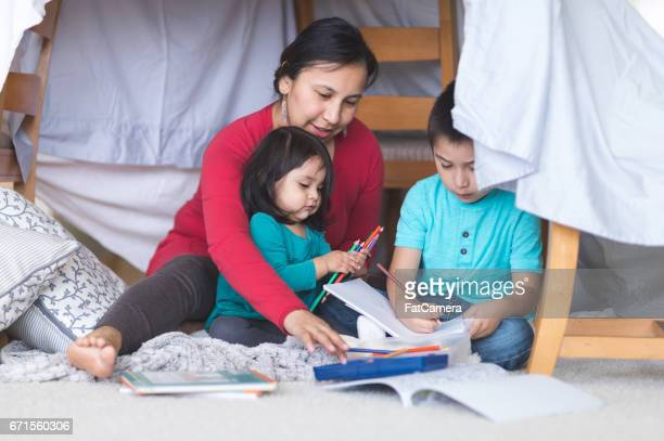 Native American mom draws with her two young children under makeshift fort in living room