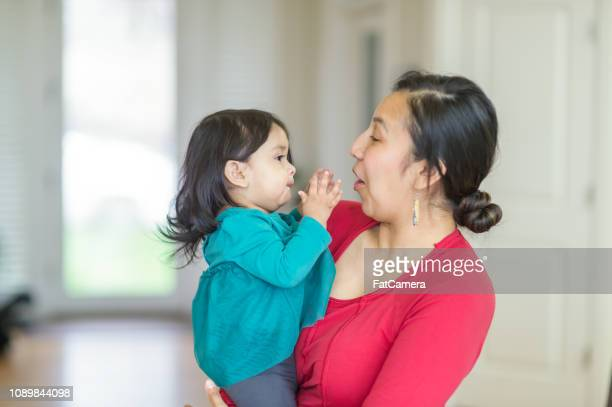 a native american mom holding her preschool-age daughter - native american ethnicity stock pictures, royalty-free photos & images