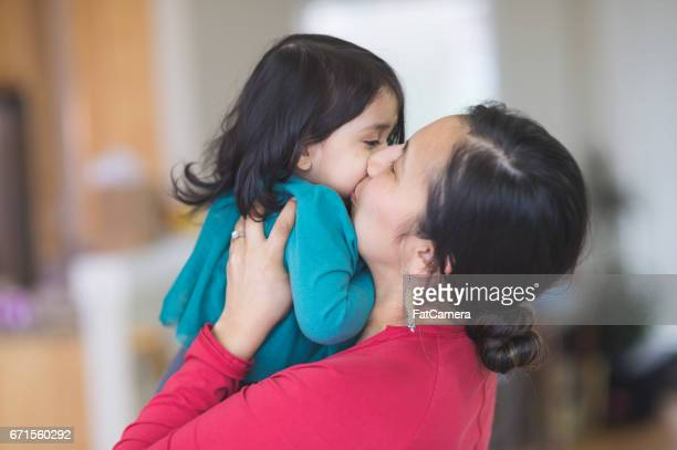 Native American mom picks up her young daughter to give her a big kiss