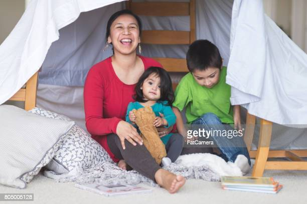 Native American mom plays with her daughter and son under makeshift fort in living room