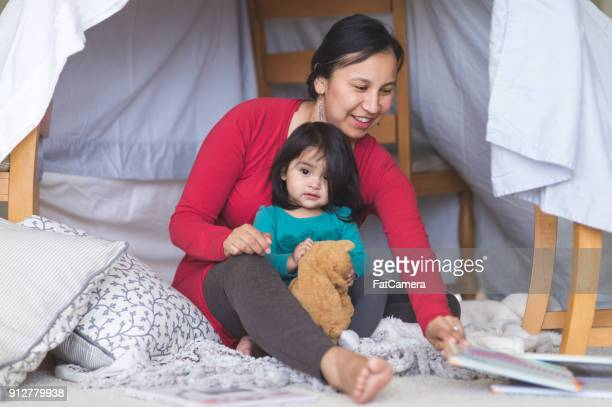 Native American mom plays with her daughter under makeshift fort in living room