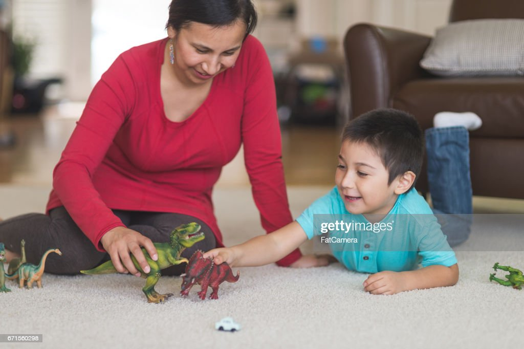 Native American mom plays with her son and toy dinosaurs on the living room floor : Stock Photo