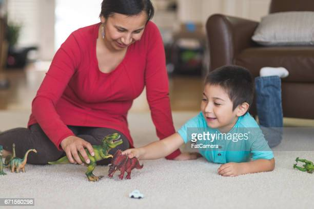 Native American mom plays with her son and toy dinosaurs on the living room floor