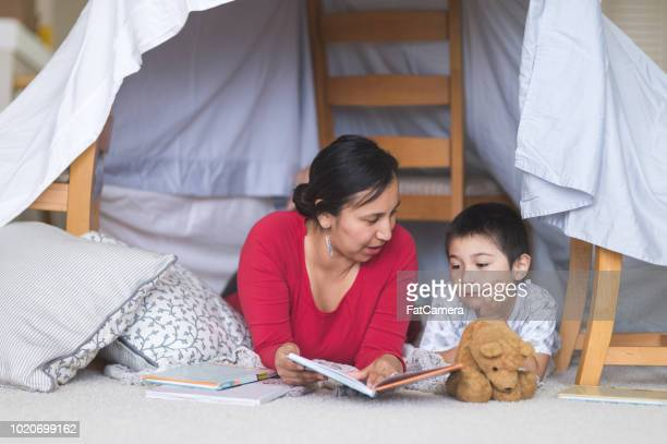 native american mom reads with her son under a makeshift fort in living room - minority groups stock pictures, royalty-free photos & images