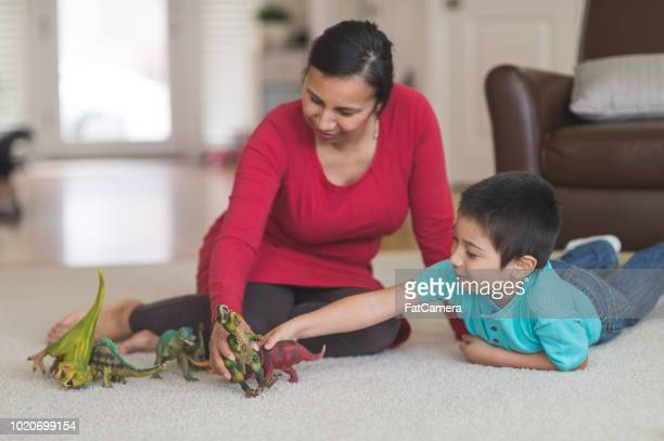 native american mother and her boy playing with dinosaurs together in the living room - indigenous peoples of the americas stock pictures, royalty-free photos & images