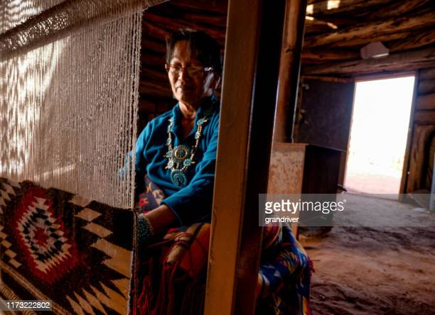 native american navajo woman in an authentic hogan weaving a traditional blanket on a loom - cherokee indian women stock pictures, royalty-free photos & images