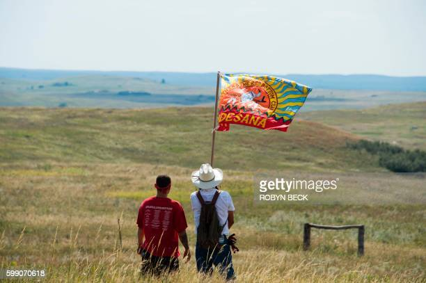 Native American protestors wave a clan flag over land designated for the Dakota Access Pipeline after protestors confronted contractors and private...