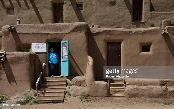 Native American resident and shop owner at Taos Pueblo in Taos New Mexico stands at his door waiting for tourists to visit his shop