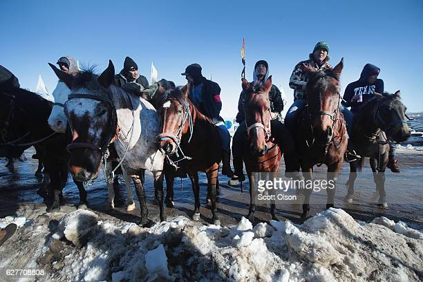 Native American riders listen at an interfaith ceremony at Oceti Sakowin Camp on the edge of the Standing Rock Sioux Reservation on December 4, 2016...