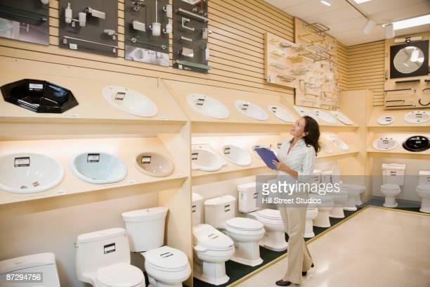 Native american saleswoman looking at sinks in plumbing showroom