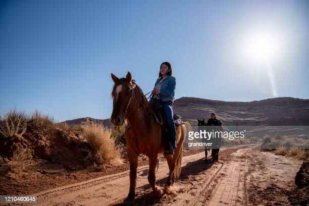 a native american sister and her brother riding horses on a dirt road with their dog - apache stock pictures, royalty-free photos & images