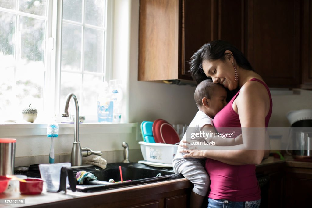 Native American Stayathome Mom Holds Baby While Leaning In