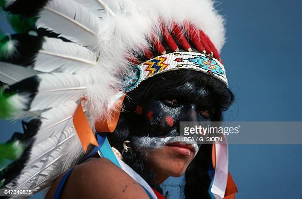 Native American with painted face and wearing a headdress with feathers annual commemoration of the Battle of Little Bighorn Montana United States of...