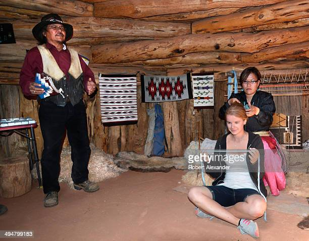 Native American woman in a traditional Navajo home demonstrates on a tourist how hair is tied in a traditional Navajo bun The demonstration is...