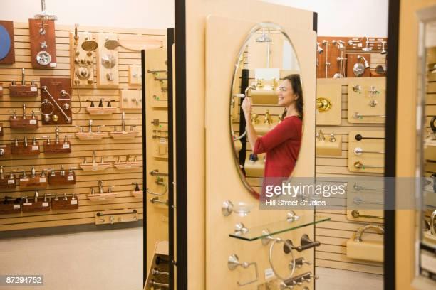 Native american woman looking at fixtures in plumbing showroom
