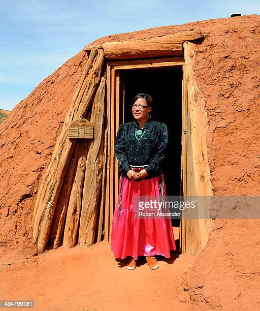 Native American woman poses for a photograph in front of a traditional Navajo home in Monument Valley Navajo Tribal Park in southeastern Utah...