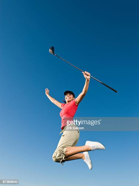 native american woman with golf club jumping in mid-air - golf humour photos et images de collection