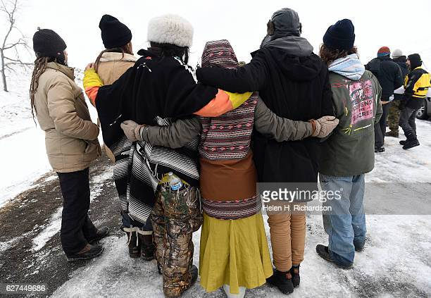 Native americans and activists stand arm and arm along the road near the Oceti Sakowin Camp on the edge of the Standing Rock Sioux Reservation on...