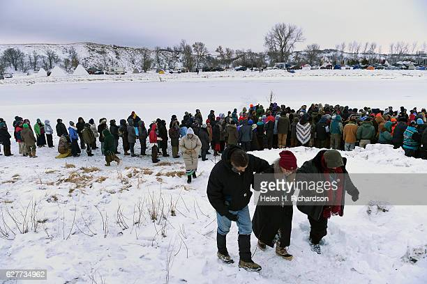 Native americans and activists take part in a prayer service by the Cannonball river at Oceti Sakowin camp on the Standing Rock Sioux Reservation on...