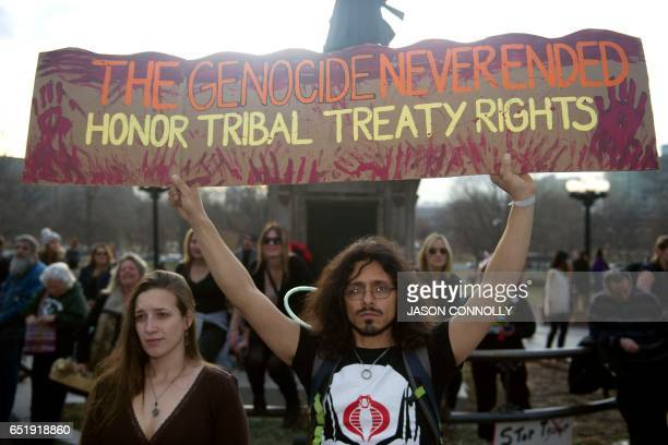 Native Americans and indigenous rights activists gather hold up a sign in protest during a Native Nations March in Denver Colorado on March 10 2017...