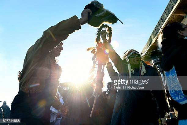 Native americans lift up their hands to celebrate their victory after Sioux Chief Arvol Looking Horse, right, announced, to members of over 300...