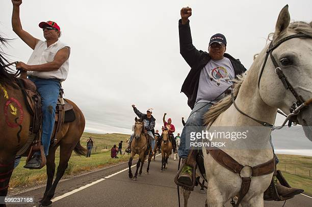 Native Americans ride with raised fists to a sacred burial ground that was disturbed by bulldozers building the Dakota Access Pipeline near the...