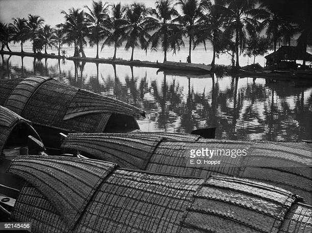 Native boats palms a lagoon and backwater in Quilon or Kollam Kerala India 1929