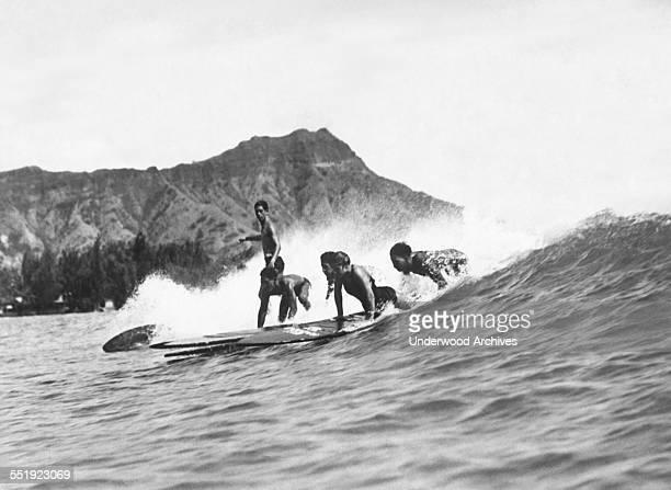 Native Hawaiians riding their surfboards at Waikiki Beach with Diamond Head in the background Honolulu Hawaii circa 1925