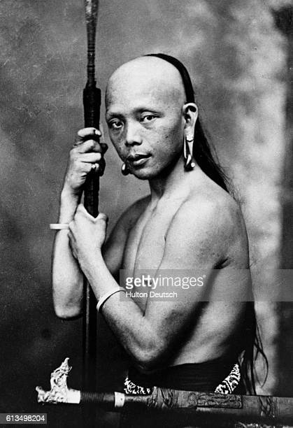 A native inhabitant of Borneo armed with a blowpipe and knife