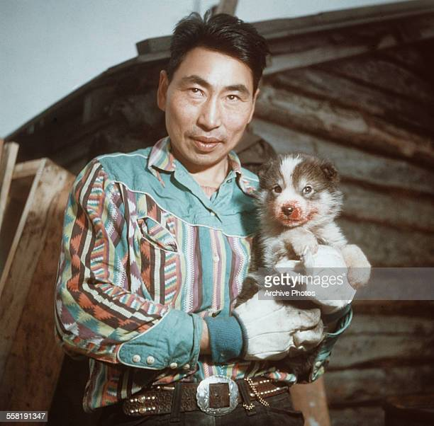 A native man with a husky puppy in Alaska USA circa 1965