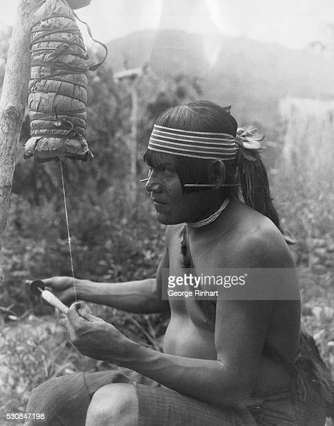 A native spinning from cotton fibres held together by a large banana leaf The male of the headhunters cares for all the arts and crafts