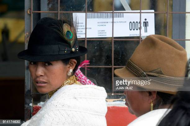 A native woman from Cangahua northeast of Quito queue outside a polling station set up at a school to cast her vote during a referendum called by...