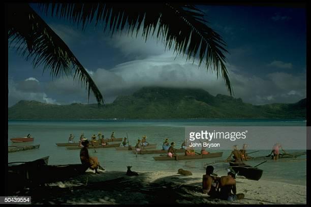 Natives in primative canoes leaving shore on Bora Bora Tahiti