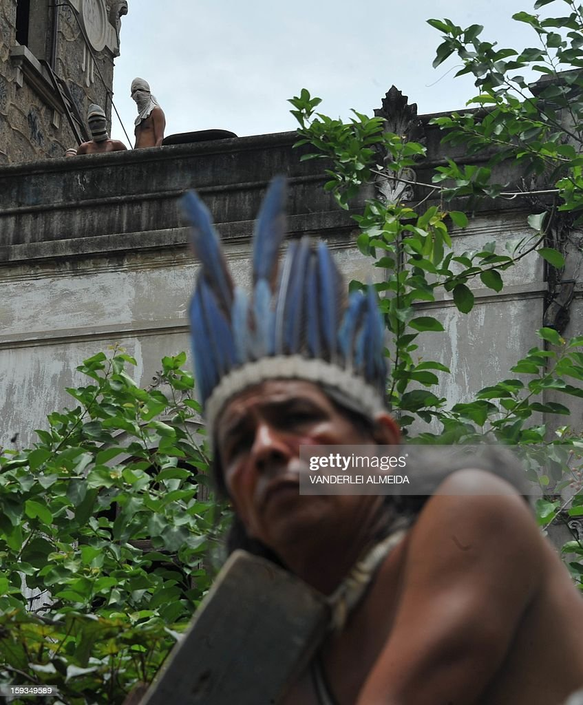 Natives look at riot police officers standing guard at the entrance of the old indigenous museum --aka Aldea Maracana-- next to Maracana stadium in Rio de Janeiro on January 12, 2013. Indians have been occupying the place since 2006 as a protest against Rio de Janeiro's governmet decision to throw them out and pull down the building to construct 10,500 parking lots for the upcoming Brazil 2014 FIFA World Cup.